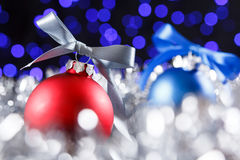 Red, grey and blue christmas balls, blured purple lights at the background Stock Photography