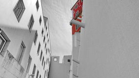 Red  on grey building. Red building among grey modern living houses Royalty Free Stock Image