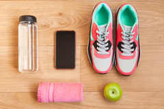 Red and grey sneakers with grey shoelaces and red towel, green apple, bottle with water, mobile phone with white headphones on woo Stock Photography