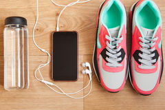 Red and grey sneakers. With grey shoelaces and bottle with water, mobile phone with white headphones on wooden background indoors Stock Image