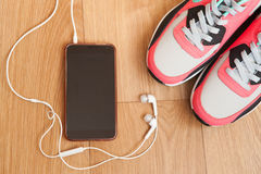 Red and grey sneakers. With grey shoelaces and mobile phone with white headphones on wooden background indoors Royalty Free Stock Images