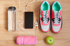 Red and grey sneakers. With grey shoelaces and red towel, green apple, bottle with water, mobile phone with white headphones on wooden background indoors Royalty Free Stock Photo