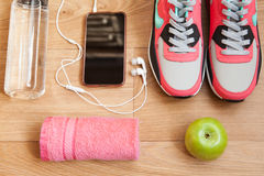 Red and grey sneakers. With grey shoelaces and red towel, green apple, bottle with water, mobile phone with white headphones on wooden background indoors Royalty Free Stock Photography