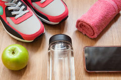 Red and grey sneakers. With grey shoelaces, red towel, green apple, bottle with water, mobile phone, on wooden background indoors Royalty Free Stock Image