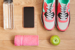 Red and grey sneakers. With grey shoelaces and red towel, green apple, bottle with water, mobile phone on wooden background indoors Stock Image
