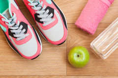 Red and grey sneakers. With grey shoelaces and red towel, green apple, bottle with water on wooden background indoors Royalty Free Stock Images