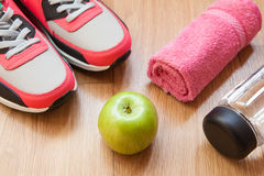 Red and grey sneakers. With grey shoelaces and red towel, green apple, bottle with water on wooden background indoors Stock Photos