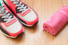 Red and grey sneakers. With grey shoelaces and red towel on wooden background indoors Stock Photos