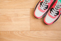 Red and grey sneakers. With grey shoelaces on wooden background indoors Royalty Free Stock Photo