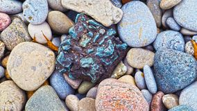 Red, grey, yellow and blue rocks. On the Ontario lake shore. Macro. Blue rock is in the middle Stock Photos