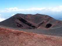 Red ground of desolate crater on volcano Etna. Red ground of desolate crater on Mount Etna, the tallest active volcano in Europe with cloudy blue sky in warm and Royalty Free Stock Photo