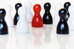 Red in a group of black and white toy figurines Stock Photography