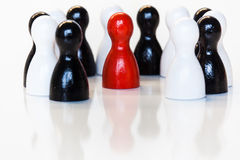 Red in a group of black and white toy figurines Royalty Free Stock Photography