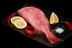 Red grouper. Fresh sea bass grill with lemon pepper and spicy on a black plate Stock Images