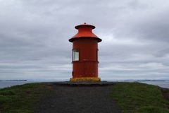 Red guardian. Red Icelandic lighthouse standing on the hill Stock Image