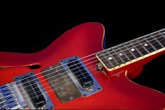 Red guitar. Isolated part of red electric guitar with strings on black background Royalty Free Stock Image