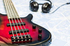 Red bass guitar. Red electric bass guitar and headphone Stock Image