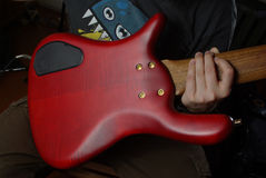 Red guitar in hand Stock Image