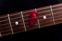 Red guitar pick on the fingerboard Stock Photo