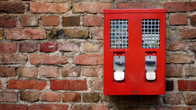 Red Gumbal, Chewing Gum Machine. Hanging on An Old Wall Royalty Free Stock Photo