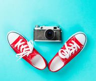 Red gumshoes and camera. On blue background Royalty Free Stock Photography