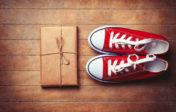 Red gumshoes and package on wooden table. Royalty Free Stock Image