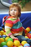 Red hair baby. Cute red hair baby is playing with colorfull balls Royalty Free Stock Photo