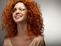 Red Hair. Beautiful Woman with Curly Long Hair and Sunglases Stock Photography
