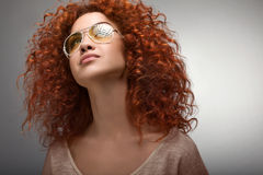 Red Hair. Beautiful Woman with Curly Long Hair and Sunglases Royalty Free Stock Photography