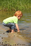Red hair boy playing in water Stock Images