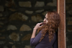 Red hair curly young woman in profile looking away with finger in mouth Royalty Free Stock Photo