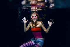 Red hair funny girl on the dark background underwater Royalty Free Stock Images