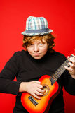 Red-hair funny teenage boy playing little guitar Royalty Free Stock Photo