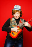 Red-hair funny teenage boy playing little guitar Stock Image