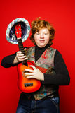 Red-hair funny teenage boy playing little guitar Stock Images