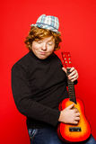 Red-hair funny teenage boy playing little guitar Royalty Free Stock Images
