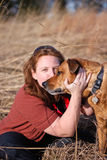 Red Hair Girl Dog Best Friends Field Outdoors. Female hugs and plays with dog on a sunny afternoon in a hayfield in Virginia Royalty Free Stock Images