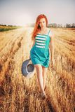 Beautiful woman in blue dress walking on the bevelled, Sun Light. Red hair girl enjoying nature in meadow. Beautiful woman in blue dress walking on the bevelled royalty free stock images