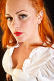 Red hair girl in pin-up style portrait shot in studio Stock Image
