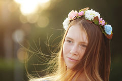 Red hair Girl Portrait in circlet of flowers  on nature green background. Cute Girl Portrait in circlet of flowers  on nature green background Stock Image