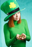 Red hair girl in Saint Patrick's Day leprechaun party hat with g. Red hair girl in Saint Patrick's Day party hat having fun with gold coins  on green grunge Royalty Free Stock Photo