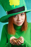 Red hair girl in Saint Patrick's Day leprechaun party hat with g. Red hair girl in Saint Patrick's Day party hat having fun with gold coins isolated on green Royalty Free Stock Photography