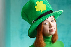 Red hair girl in Saint Patrick's Day leprechaun party hat. Red hair girl in Saint Patrick's Day party hat having fun on green grunge background Stock Images