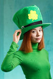 Red hair girl in Saint Patrick's Day leprechaun party hat. Red hair girl in Saint Patrick's Day party hat having fun isolated on green grunge background Stock Photography