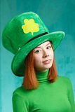 Red hair girl in Saint Patrick's Day leprechaun party hat. Red hair girl in Saint Patrick's Day party hat having fun isolated on green grunge background Royalty Free Stock Photos