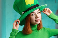 Red hair girl in Saint Patrick's Day leprechaun party hat. Red hair girl in Saint Patrick's Day party hat having fun isolated on green grunge background Royalty Free Stock Photo