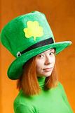 Red hair girl in Saint Patrick's Day party hat. Having fun isolated on orange grunge background Stock Images