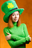 Red hair girl in Saint Patrick's Day party hat. Having fun on orange grunge background Royalty Free Stock Photography
