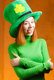 Red hair girl in Saint Patrick's Day party hat. Having fun on orange grunge background Stock Photos