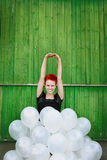 Red hair girl with silver balloons. Green wall Royalty Free Stock Image